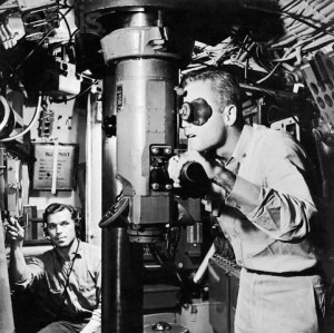 Sailor looking through a submarine periscope